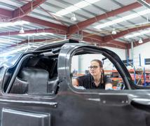 Female engineer inspecting carbon fibre body in racing car factory - stock photo