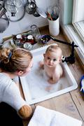 Overhead portrait of baby boy bathing in kitchen sink - stock photo