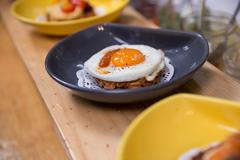 Row of fried egg meals on cooperative food market stall - stock photo