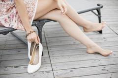 Waist down view of young woman removing high heels on park bench - stock photo