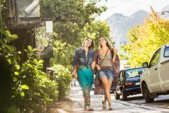 Two women friends strolling on roadside  arm in arm, Franschhoek, South Africa Stock Photos