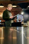 Male coffee shop owner at coffee roaster with clipboard Stock Photos