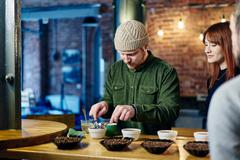 Coffee shop team preparing bowls of coffee and coffee beans at tasting Stock Photos