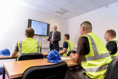 Apprentice builders in presentation in training facility Stock Photos