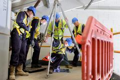 Apprentice builders learning how to use hoist in training facility - stock photo
