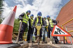 Apprentice builders training with pneumatic drill in training facility - stock photo