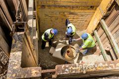 Apprentice builders training with drainage in hole on building site - stock photo