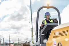 Apprentice builders training with road roller on building site Stock Photos