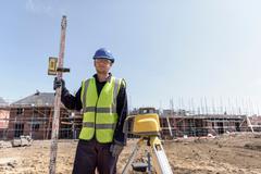 Apprentice builder with laser leveller on building site - stock photo