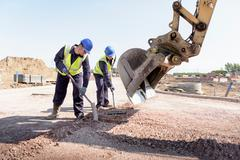 Apprentice builders levelling road with digger on building site - stock photo