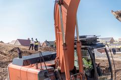 Excavator and builders on housing building site - stock photo