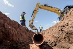 Builders laying pipework on housing building site - stock photo
