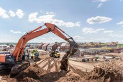 Excavator moving earth on housing building site Stock Photos