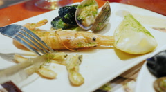 Close-up - eat seafood. On a plate the knife cuts the mollusk - stock footage