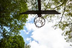 Low angle view of basketball hoop silhouetted against blue sky - stock photo