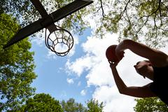 Low angle view of silhouetted young man aiming ball at basketball hoop - stock photo