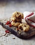 Oat and cranberry cookies, rustic wooden board, vintage tea towel, wooden table - stock photo
