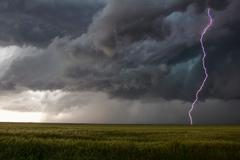 A smooth channel lightning bolt arcs to the ground through the turbulent updraft - stock photo