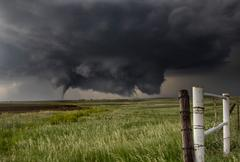 A large cone tornado touches down in an open country field from a very large Stock Photos