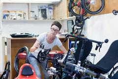 Woman in bicycle workshop checking pedal on recumbent bicycle - stock photo