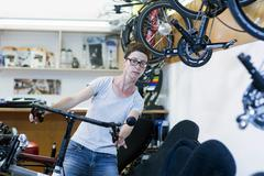 Woman in bicycle workshop checking handlebars on recumbent bicycle - stock photo