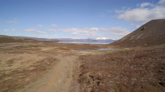 Aerial view over volcanic landscape with rock and lake -  Iceland Stock Footage