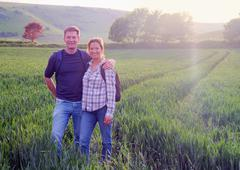 Couple in field looking at camera smiling - stock photo