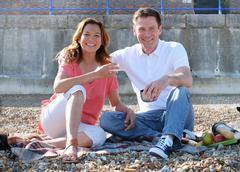 Couple sitting on shingle beach having picnic looking at camera smiling - stock photo