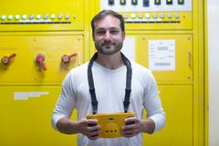 Man in front of yellow control panel smiling Stock Photos