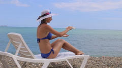 Woman applying sunscreen to her shoulder on a warm near the sparkling sea Stock Footage
