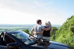 Mature couple sitting on convertible car looking at view - stock photo
