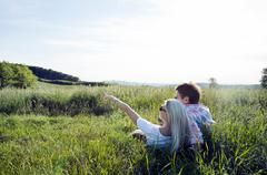 Mature couple lying in field Stock Photos