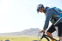Side view of cyclist cycling on hillside Stock Photos
