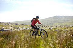 Cyclist cycling on hillside - stock photo