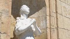 Statue of praying saint woman and a fly Stock Footage