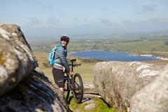 Cyclist with bicycle on rocky outcrop - stock photo