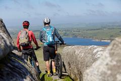 Cyclists with bicycles on rocky outcrop - stock photo