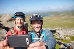 Cyclists with on rocky outcrop taking selfie - stock photo