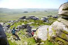 Cyclists carrying bicycles on rocky outcrop - stock photo