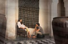 Young couple sitting on chair and pouffe chatting, Marrakesh, Morocco - stock photo