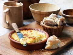 Baked cheese in terracotta dish Stock Photos