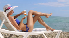 Woman applying suntan cream. Close up view on the legs. Stock Footage