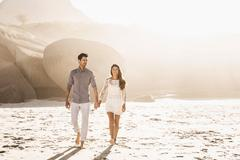 Couple strolling on sunlit beach, Cape Town, South Africa Stock Photos