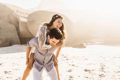 Man giving girlfriend a piggy back on sunlit beach, Cape Town, South Africa Kuvituskuvat