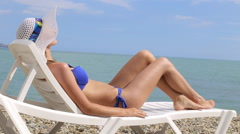 Young woman relaxing on tropical beach lying on beach lounger Stock Footage