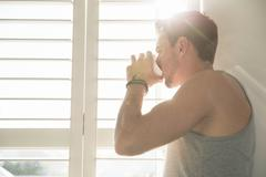 Young man drinking coffee and looking through sunlit bedroom window in morning Stock Photos