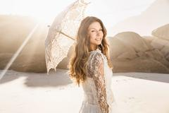 Portrait of beautiful woman holding parasol looking over her shoulder on sunlit - stock photo