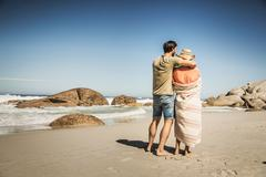 Rear view of couple wrapped in blanket looking out from beach, Cape Town, South - stock photo