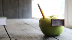 Back to school background - inscription and pencil and apple on the table - stock footage