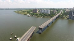 Aerial video, lift up of bridge on river against the background of city, 4k Stock Footage